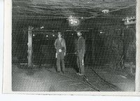 Two coal miners inside the mines standing on the tracks