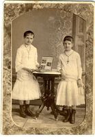 Photograph of two girls looking through a photo album in 1879