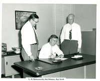 L.H. Butterworth, Jim Delaney and Ray Koch at Desk in Office