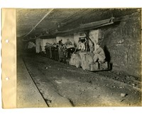 Shift workers riding on rail carts in the mines