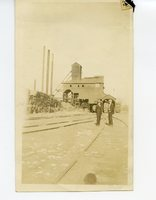 Young men standing outside of coal mine #2 by lumber stacks in Glen Carbon, Illinois.