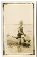 Photograph of a young boy on a floatie in a lake