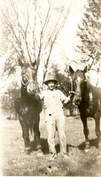 Photograph of Charlie Glassmaker with two horses on the Mudge farm in Grantfork