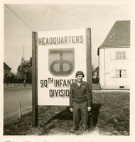 Ray Bieser in front of 90th Division sign at Headquarters in Germany in 1945