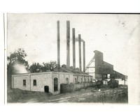 The back of the coal mine against the railroad tracks. Railroad carts filled with coal.