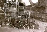 Group Photograph of Miners in Uniforms in Front of Equipment