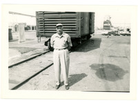 1952 Man Posing in Front of Boxcar